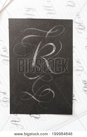 calligraphy, occasion, painting concept. on the dark black very textured paper there is big latin letter r inscribing with white ink and decorated with elegant ornamentation