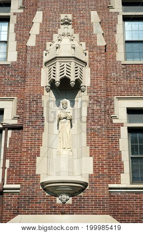 JOLIET, ILLINOIS / UNITED STATES - JULY 17, 2017: A sculpture of Saint Francis stands in a recess in the wall of Tower Hall at the University of Saint Francis.