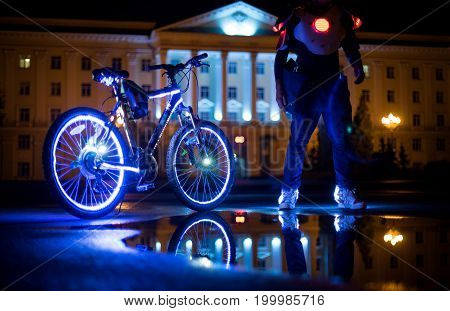 Glowing bicycle is reflected in the water. LED strip backlight. Nearby is a man in luminous shoes