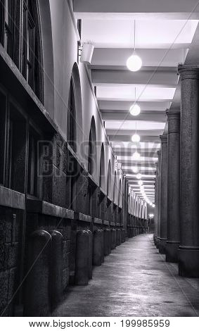 Corridor under a building in the old city center of Ljubljana the capital of Slovenia composed of tall imposing columns with an endless effect.