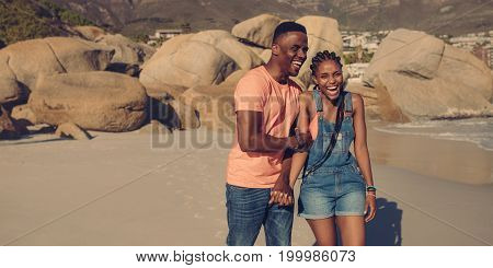Horizontal shot of young couple on summer vacation laughing at the beach. African man and woman walking and smiling along the seashore.
