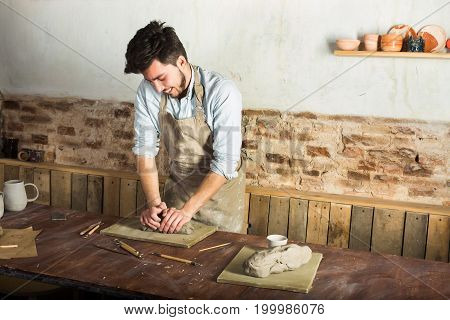 potter, workshop, ceramics art concept - smiling young brunette man dressed in an apron, male hands kneading the fireclay, a ceramist with raw material on wooden table with sculpting tool set, jugs