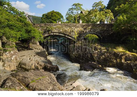 Betws y Coed Wales UK - August 15 2017: The Pont-y-Pair Bridge or Bridge of the Cauldron over the River Llugwy dated from 1475 and is the oldest existing bridge in the village