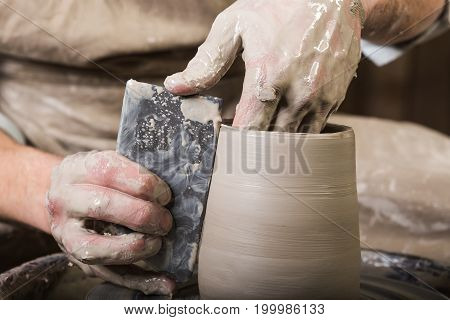 pottery, workshop, ceramics art concept - closeup on male fingers sculpt new utensil with a tools and water, man's hands working with potter's wheel and raw fire clay, close view