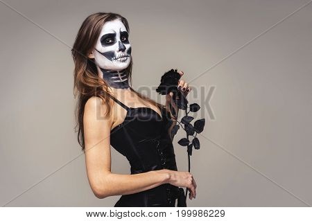 Portrait of woman with halloween skeleton makeup holding black rose flower over gray background.