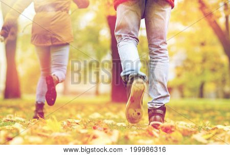 love, relationships, season and people concept - young couple running in autumn park