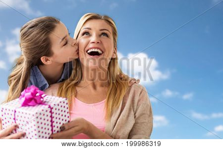 people, holidays and family concept - happy girl giving birthday present to mother over blue sky and clouds background