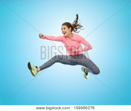 sport, fitness, motion and people concept - happy young woman jumping in air in fighting pose over blue background