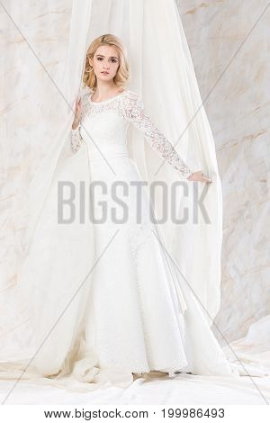 fashionable white gown, beautiful blonde model, bride hairstyle and makeup concept - seductive young woman in wedding dress standing indoors on light background, slim female posing near curtains