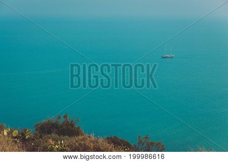 Beautiful landscape with the horizon of the sea and a sailboat in the calm waters of the sea in the afternoon. Minimal style with colorful clouds and sky background.