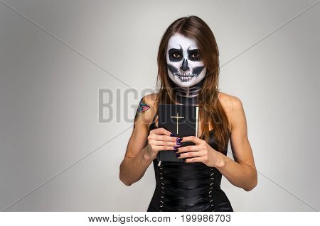 Portrait of young beautiful girl with fearful halloween skeleton makeup holding Holy Bible over gray background