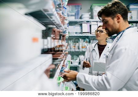 Two pharmacist working in drugstore. Male and female pharmacists checking medicines inventory at hospital pharmacy.
