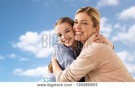 people and family concept - happy smiling girl with mother hugging over blue sky and clouds background