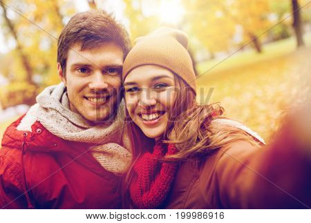 love, technology, relationship, family and people concept - happy smiling young couple taking selfie in autumn park