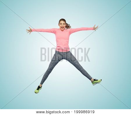 sport, fitness, motion and people concept - happy smiling young woman jumping in air over white background