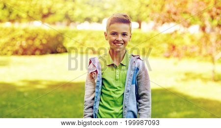 childhood and people concept - happy smiling boy at summer park