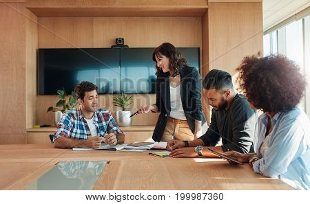Multiracial business people meeting around a table and discussing new strategies. Creative team of professionals meeting in conference room.