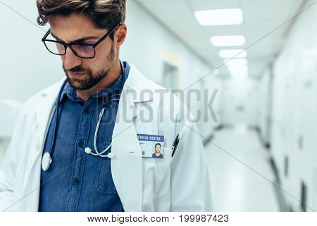 Close up of male doctor in hospital corridor. Caucasian medicine practitioner walking through healthcare center hallway.
