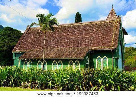Waioli Huiia Church built in 1843 by missionaries surrounded by lush green tropical gardens taken at Hanalei Bay in Kauai, HI