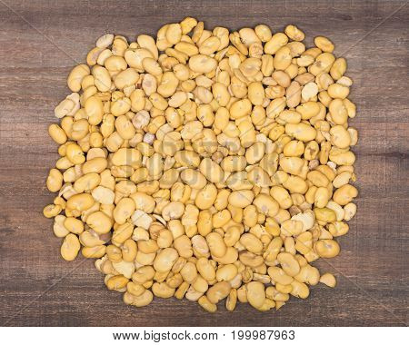Organic dry broad haba beans on wooden vintage background