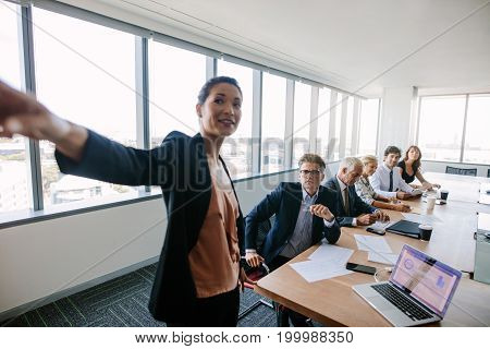 Corporate professionals sitting around conference table and concentrating at woman giving business presentation. Multi-ethnic business group at presentation.