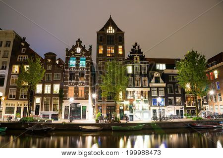 Amsterdam, Netherlands - April 20, 2017: Amsterdam canal Singel with typical dutch houses and houseboats by night, Holland, Netherlands.