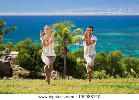 fitness, sport and people concept - smiling couple making yoga in eagle pose outdoors over natural background