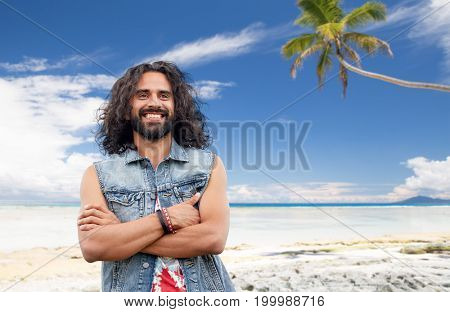 travel, tourism and people concept - smiling young hippie man in denim vest over tropical beach background