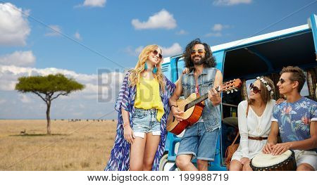 summer holidays, road trip, travel and people concept - happy young hippie friends with guitar and drum playing music at minivan car over african savannah background