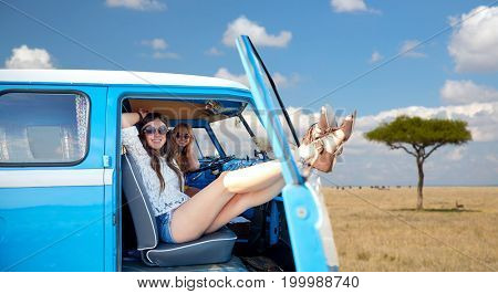 summer holidays, road trip, travel and people concept - smiling young hippie women resting in minivan car over african savannah background