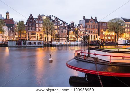 Amsterdam, Netherlands - April 21, 2017: Canals of Amsterdam at night. Amsterdam is the capital and most populous city of the Netherlands.