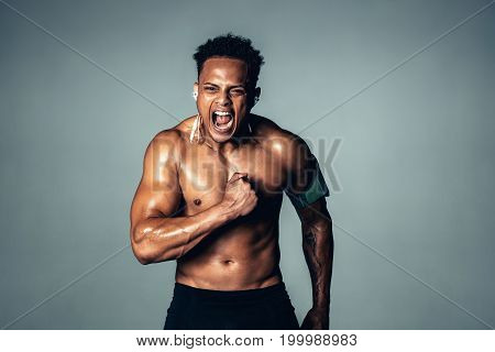 Shirtless male model with muscular physique shouting. Aggressive young man screaming against grey background.