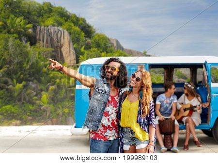 summer holidays, road trip, travel and people concept - smiling young hippie couple with friends in minivan car over exotic island beach background