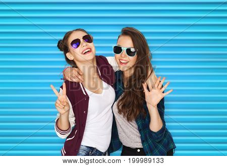 people, summer and fashion concept - happy smiling pretty teenage girls or friends in sunglasses showing peace hand sign over blue ribbed background