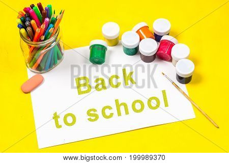 The Inscription - Back To School, On A Sheet Of White Paper Surrounded By Colored Pencils, Markers,