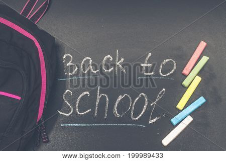 Back To School Message On Blackboard Inscribed With Colorful Chalk For Background. Backpack.