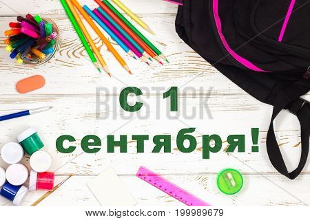 The Inscription In Russian Is September 1. School Supplies On A White Wooden Background With An Empt