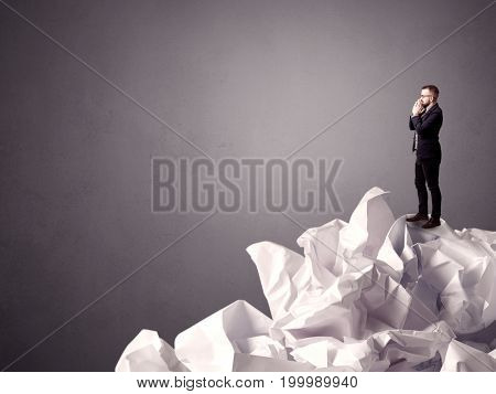 Thoughtful young businessman standing on a pile of crumpled paper with a grungy grey background