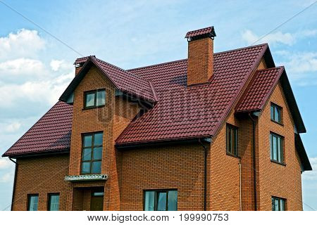 Modern brown brick house against the sky and clouds