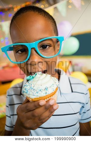 Portrait of cute boy having cupcake during birthday party at home