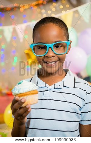 Portrait of cute boy holding cupcake during birthday party at home