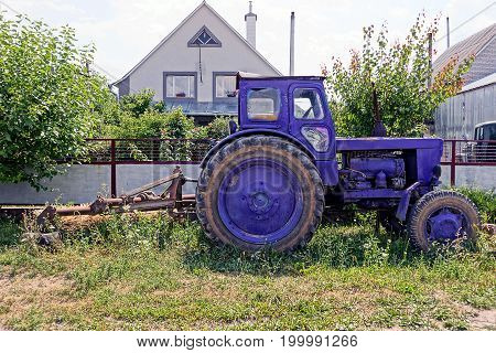 Lilac old tractor stands in a rural yard in the grass