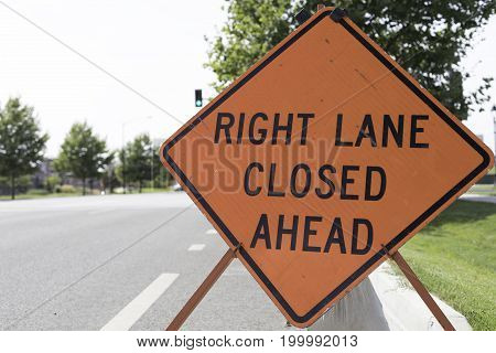 Right lane closed ahead sign posted in the street