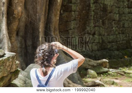 European tourist taking picture of temples of Angkor ruins.