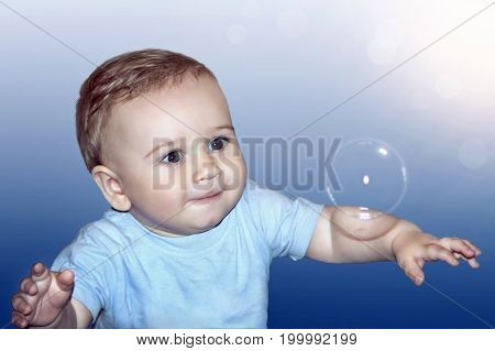 cute baby with curiosity looks at a soap bubble.blue background