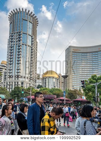 Shanghai, China - Nov 6, 2016: Crowds on Nanjing Road Pedestrian Street. Modern buildings and afternoon dramatic cloudscape feature in the background.