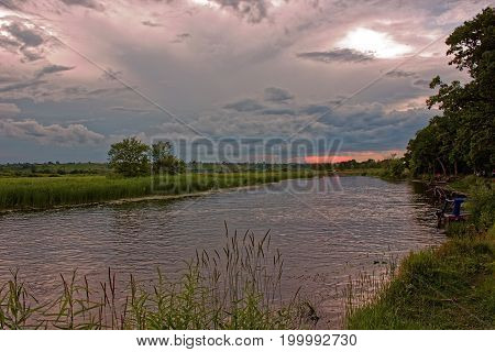 A quiet summer evening on the bank of the river at sunset.