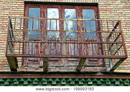 The old rusty metal frame of the balcony on the wall of the house