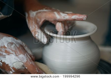 Potter works at pottery wheel, dirty woman hands, selective focus