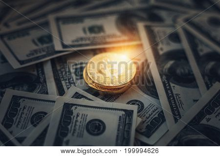 Glowing and shining coin Bitcoin on a dark background of paper American dollars money, selective focus, toned